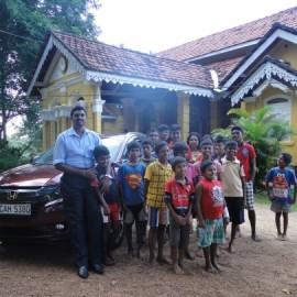 Projektmanager mit neuem Auto und Jungen aus dem Heim in Hikkaduwa