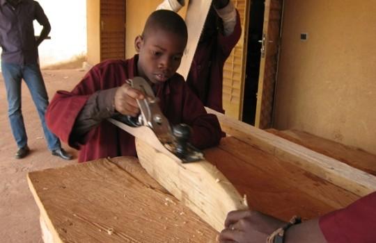 Ein Junge lernt das Schreinerhandwerk
